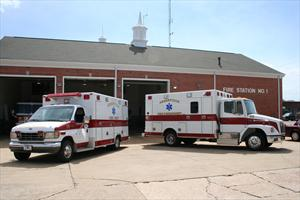 Two Ambulances Parked Outside Fire Station